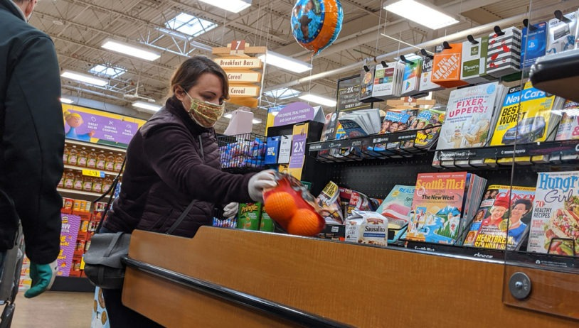woman placing items on checkout counter at grocery store