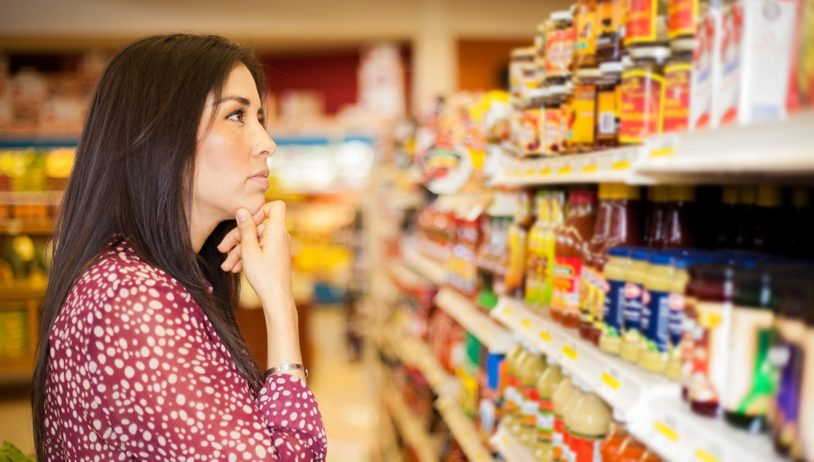 A woman looking at some shelves in a supermarket trying to decide what to buy