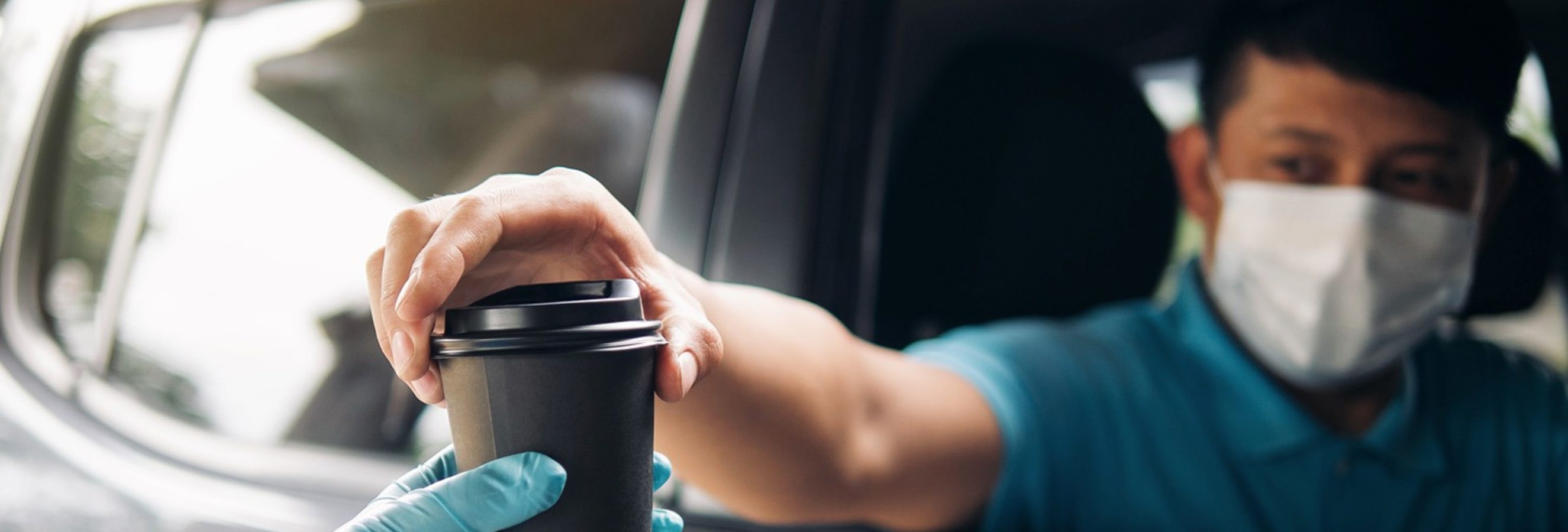 man being handed a coffee at drive-thru
